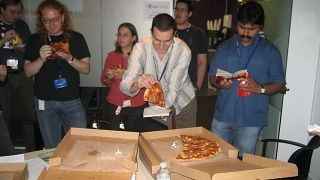 People eating pizza at BarCamp London.jpg