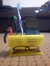 Multipurpose cell-phone dock with slots for stationery and a pair of specs.jpg